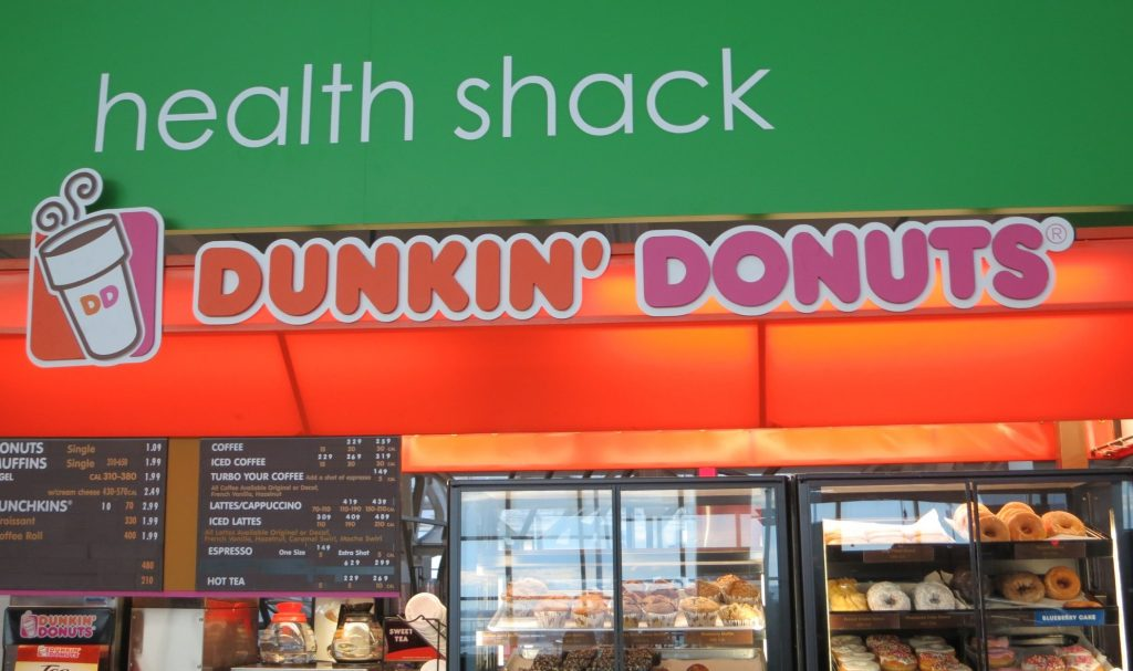 "A Dunkin Donuts sign under a sign reading ""health shack"" at Kennedy Airport in New York CIty"