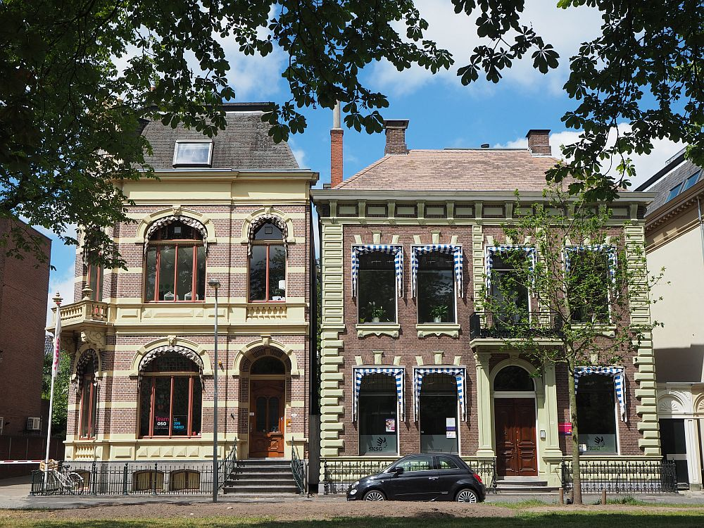 Two houses, each about 2 stories. Both are in redbrick. The left-hand one has big arched windows and beige horizontal stripes among the brick rows. It has a mansard roof. The one on the right is also red brick with beige detail, but the detail is less: only above the windows and beside the front door. These windows are square rather than arched and have shades, which are blue and white striped but now closed. Groningen has been a great place to live as an expat, without the cost of living they have in places like Amsterdam.