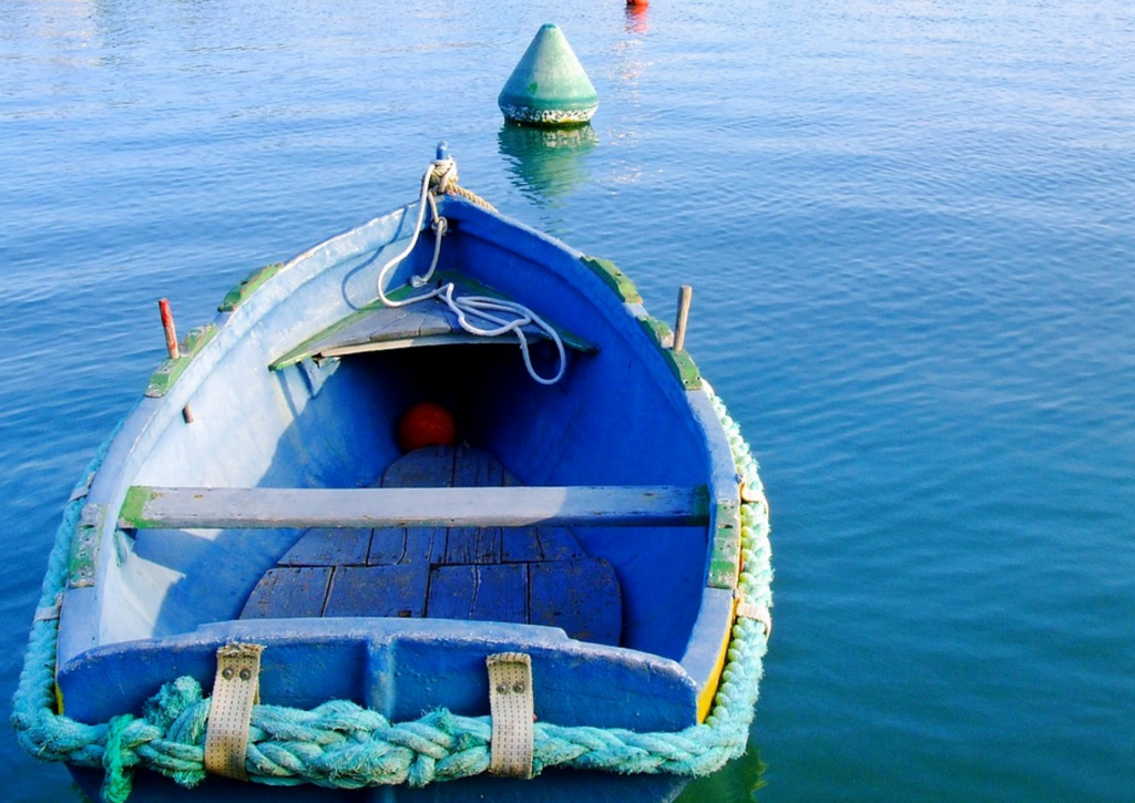 A green and blue rowboat, moored to a buoy. Somewhere in Vietnam, maybe?