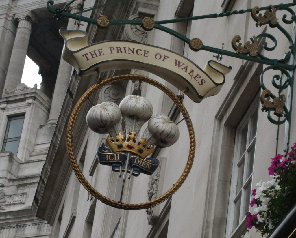 "The Prince of Wales pub in London, whose sign includes a crown, three feathers, and the words ""Ich dien."""