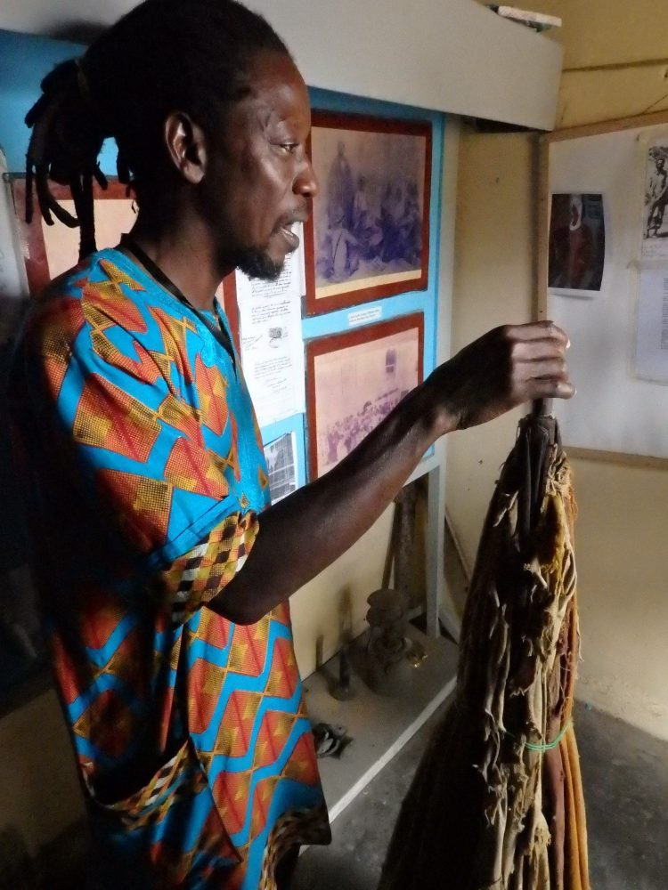 Simon, our guide at Badagry, has dreadlocks held back in a ponytail and wears a brightly-colored Nigerian style shirt. He holds the tip of the umbrella, which is bundled closed, and probably rests on the floor outside the picture. It reaches to about his shoulder height. It's a deep red color in very poor condition, but still gives an idea of what a hard job it must have been for the slave who had to hold it all the time.
