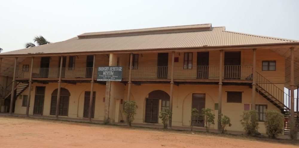 "A wide, low building of two stories, with the roof extending forward over a balcony that runs the entire length of the building. Along both shaded floors are several doorways and, on the ground floor, two archways as well. A sign in the middle reads ""Badagry Heritage Museum."""