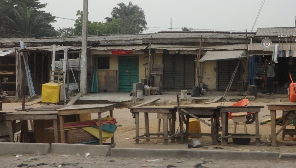 a typical row of shops in Lagos, Nigeria, many closed since it was a Sunday morning