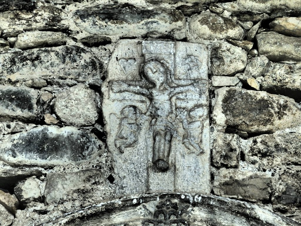 carving above the doorway of the Sant Andreu church in Casau, Val d'Aran, Spain