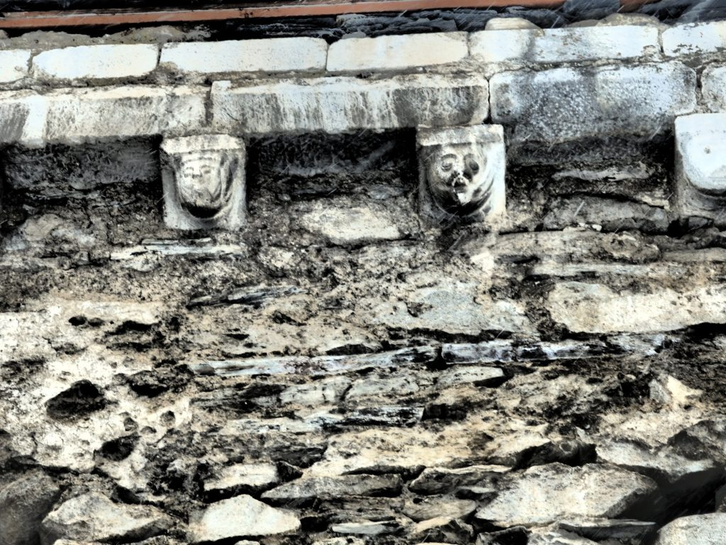 small carved figures under the eaves of the church at Unha, in the Val d'Aran, Spain