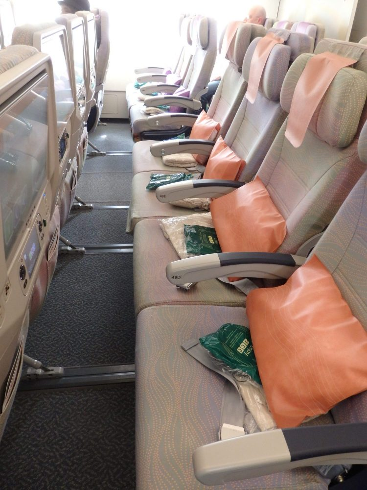 This gives an idea of the seat pitch on the Emirates A380: an empty row of seats (4 seats are visible), then an aisle and three more seats beyond that. Chairs are beige, with orange pillows on each one and and orange cloth on each headrest.