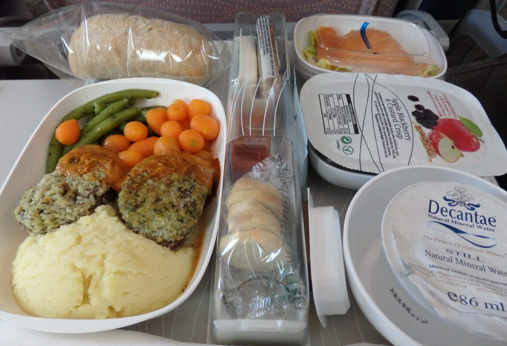 My dinner on an Emirates A380 flight. The box in the center contains snacks for later. The box on the left has some sort of meat patties, mashed potatoes, carrots and green beans. Behind that is a bread roll in plastic. On the right is a container of mineral water, a container of apple blackberry and custard crisp and, in the background, a salad.