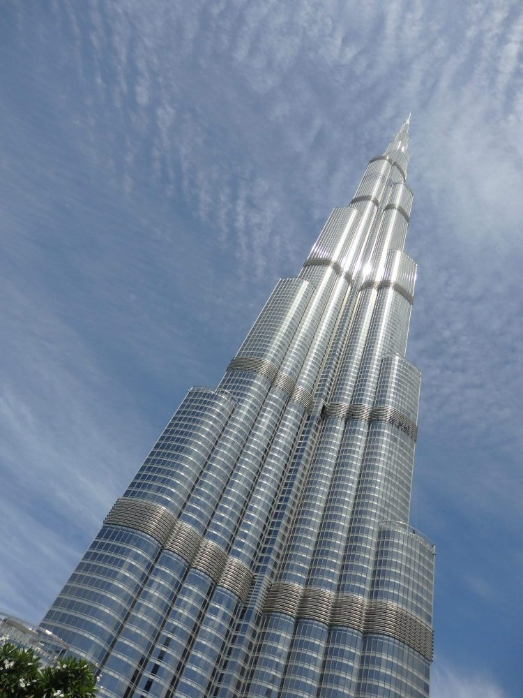 The burj khalifa is shaped like a tall bundle of flattened cylinders, some of which end at a lower level than others, so that the tip is a single point. In this photo it's shown at an angle in order to fit it into the picutre, and the top is not really visible.