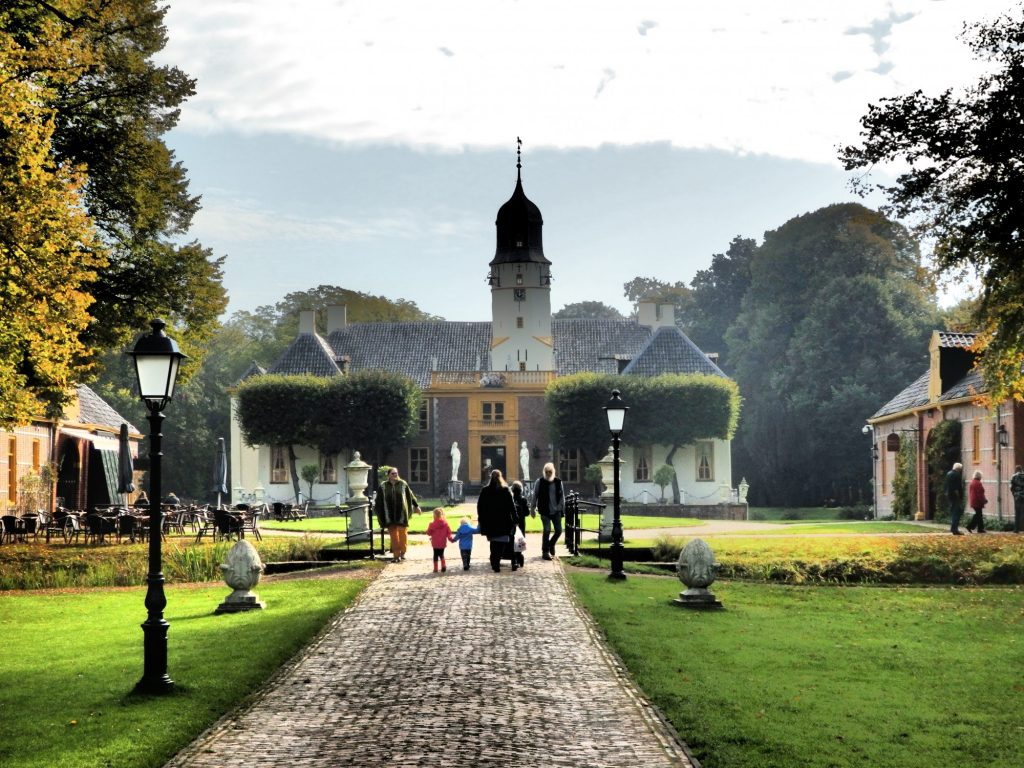 Fraeylemaborg, with the restaurant on the left and coach house on the right. The photo sights straight down the approaching brick walk toward the entrance to the main house. The main house is low and white, with a row of carefuly pruned trees hiding much of the facade. A tower rises behind them, off center from the central entrance.