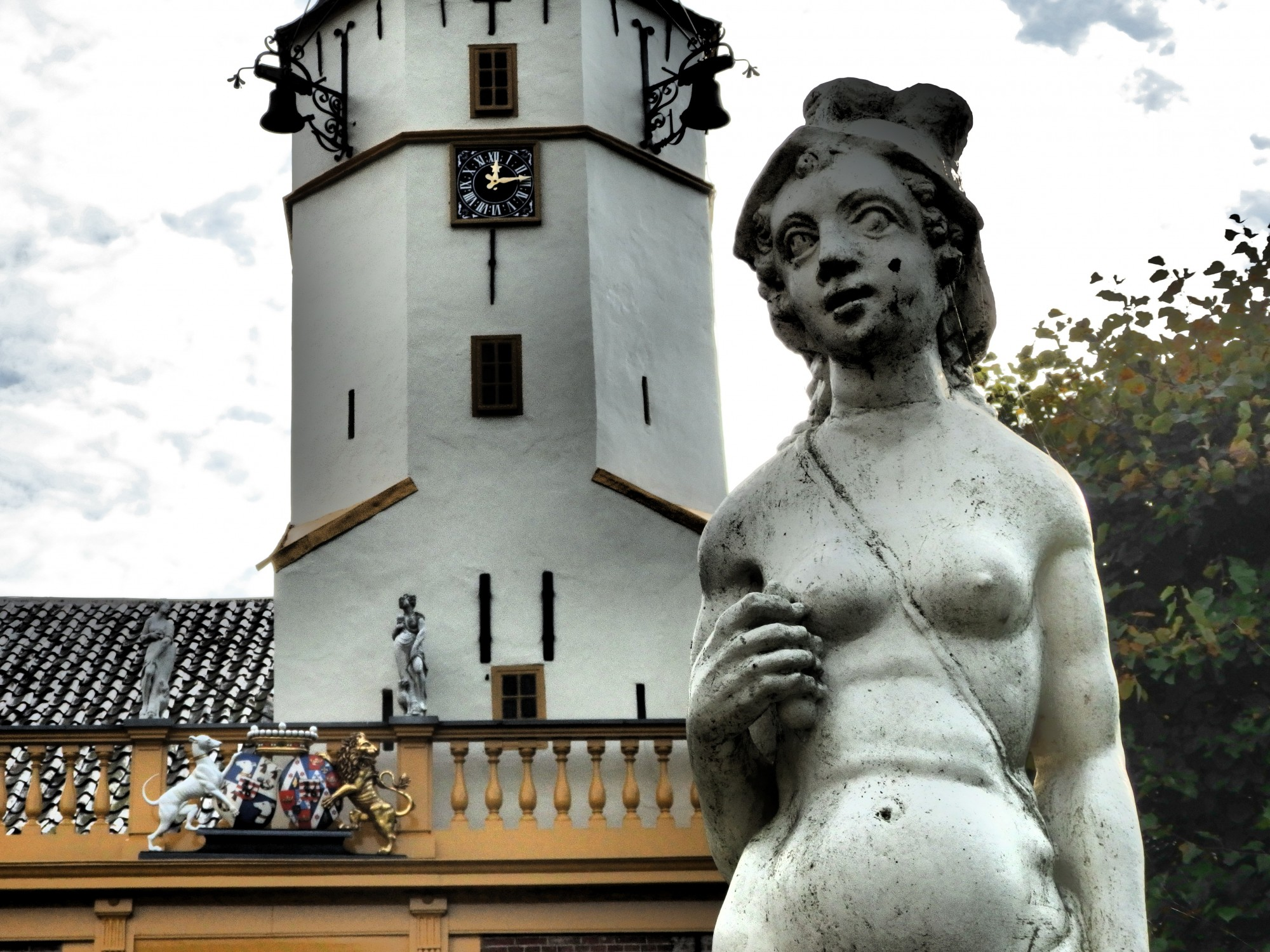 a statue in front of Fraeylemaborg, in Slochteren, the Netherlands. Notice the family crest above the entrance.