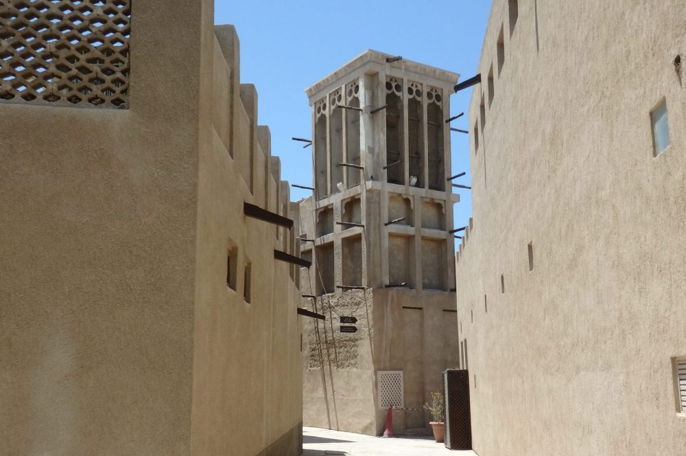a wind tower on a narrow street in Old Dubai