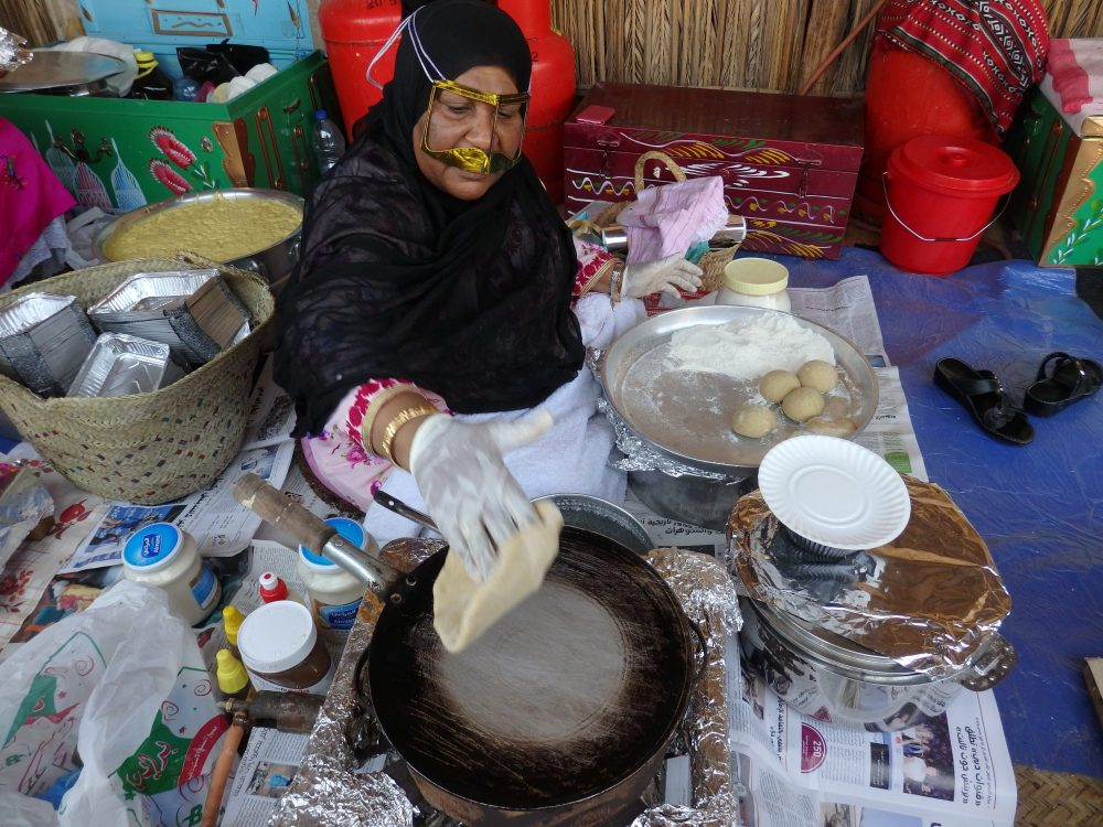 woman preparing my khamer bread with egg and cheese in Heritage Village in Old Dubai