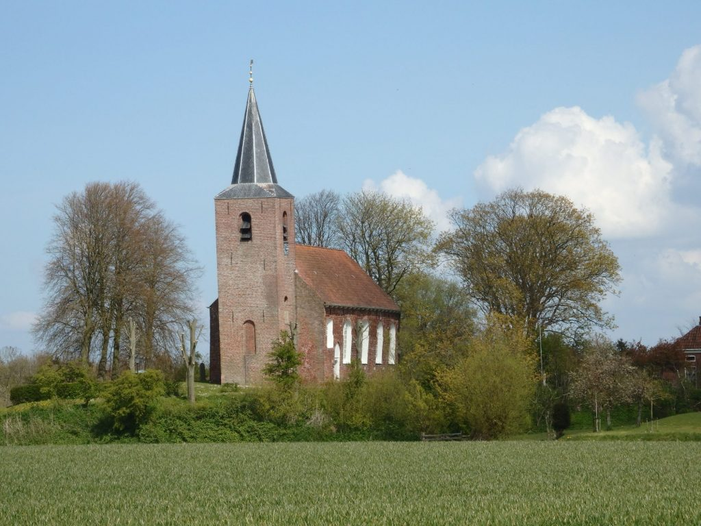 A very small, very simple red-brick church: rectangular, white-edged windows on the side, standing on a slight rise, with a square tower a bit taller than the building in front. The tower has a black pointed roof and leans slightly to the left. In the foreground, a grassy field. A few trees dot the rise (terp) around the church.