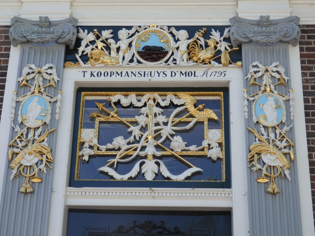 "In the square above the door as well as above and beside it are some lavish carvings: feathers, arrows, banners of all sorts, mostly in white or gold. Above the door frame it reads ""'t Koopmanshuys d'Mol A1795."""