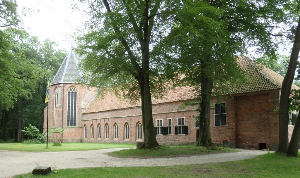 A low, long, red-brick building with what looks like a church attached at one end: it has tall arched windows. In front of the building is a grassy area with some large trees.