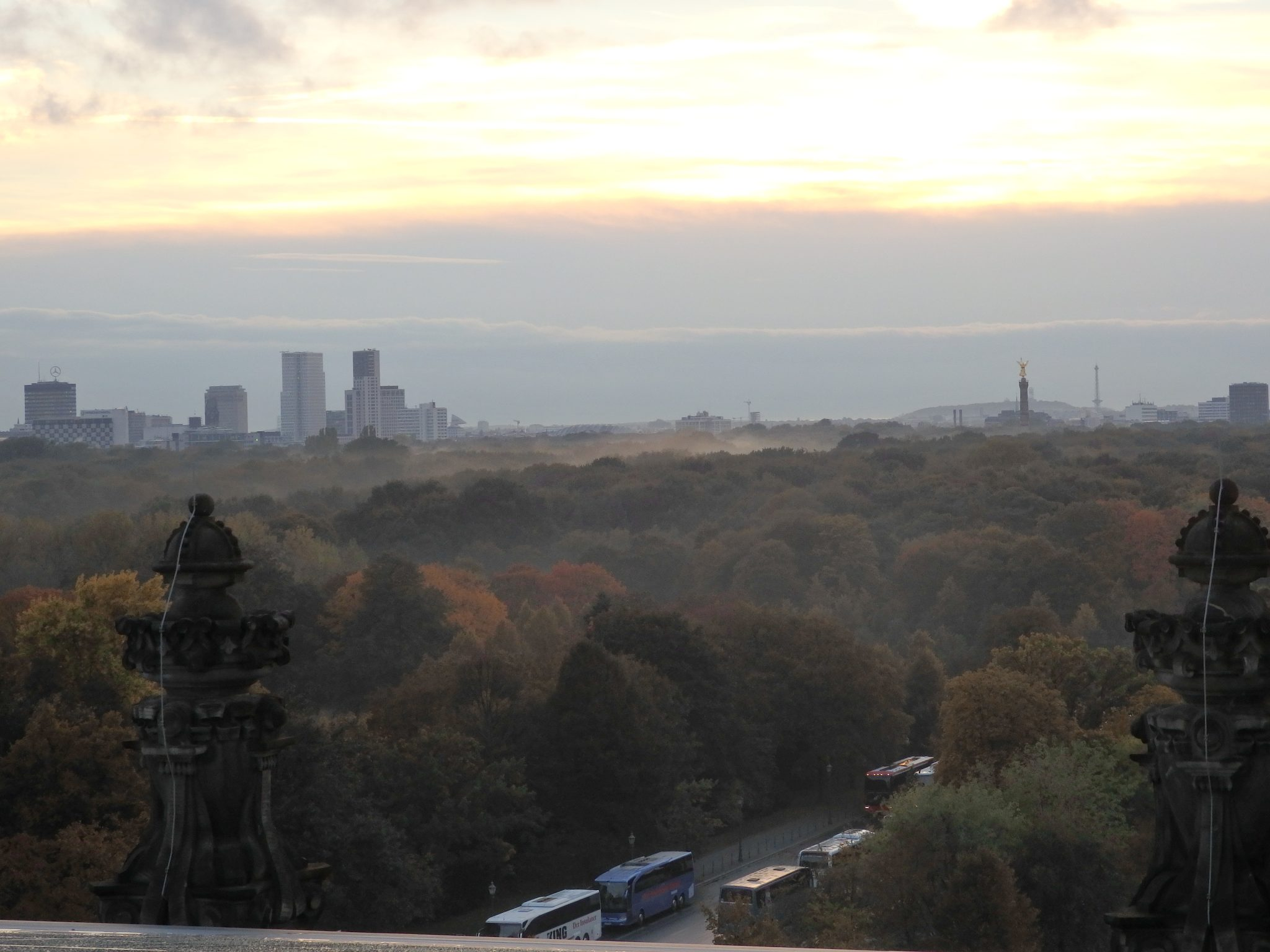 "Our sunset ended in a bank of clouds on the horizon. In the foreground, the Tiergarten park. The buildings in the distance on the left are the ""City West"" district around Kurfurstendamm. The pillar on the right is the Victory Column at Grosser Stern."