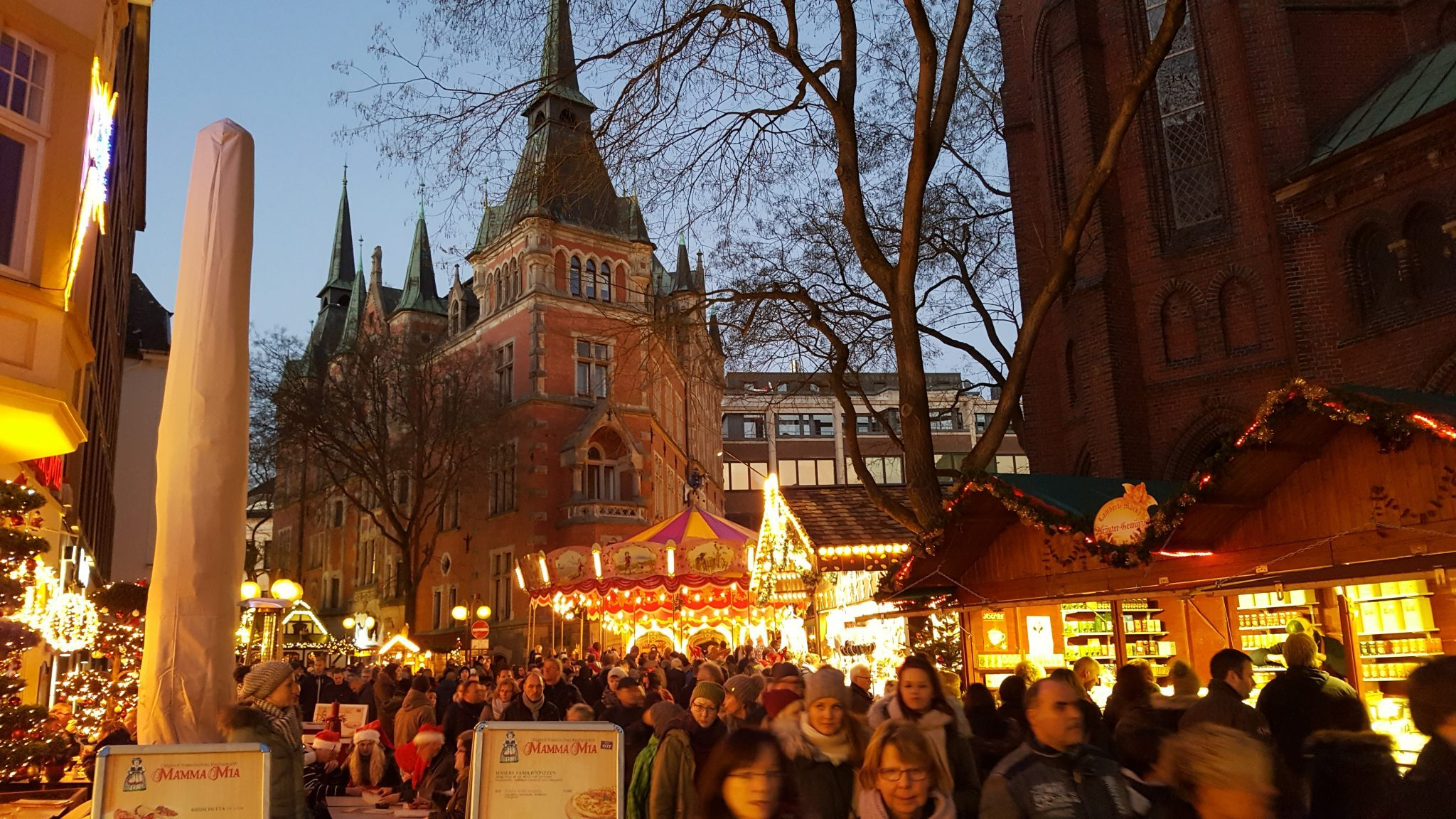 One of many Christmas Markets in Germany; this is Oldenburg. In the background, the rathaus (city hall). On the right, the St. Lamberti church looms behind the brightly-lit stalls.