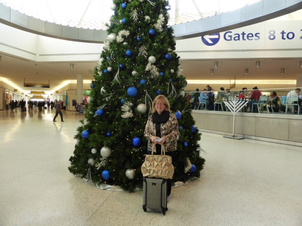 Irene poses in front of a tall Xmas tree with blue and white balls, in the middle of an open space inside an airport. She wears a warm jacket and has a grey wheeled bag and a large handbag. Behind her a sign is visible pointing to gates. Christmas in the airport. Photo courtesy of Irene S. Levine