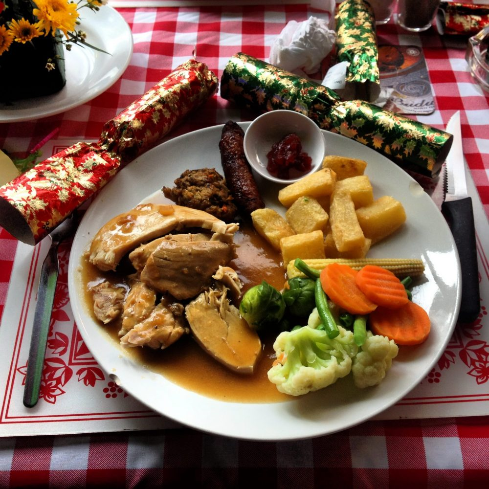 A plate of food that includes some sort of meat with brown gravy, some fries, mixed vegetables, and a few other small items I can't identify. Next to the plate are two Xmas crackers. Photo courtesy of Jane Dempster-Smith