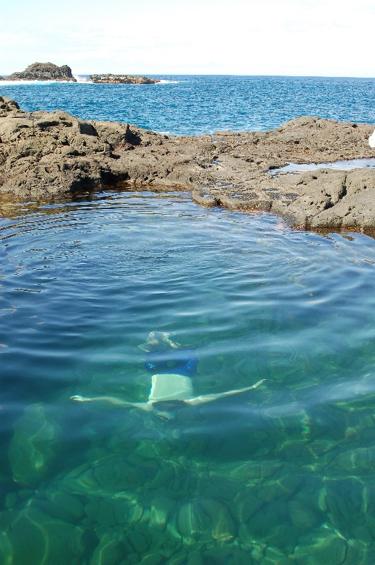 One person is visible, swimming toward the camera, under the water's surface. The water is clear and bluish-green and some rocks emerge from the water behind the swimmer. Photo courtesy of Nat Harris