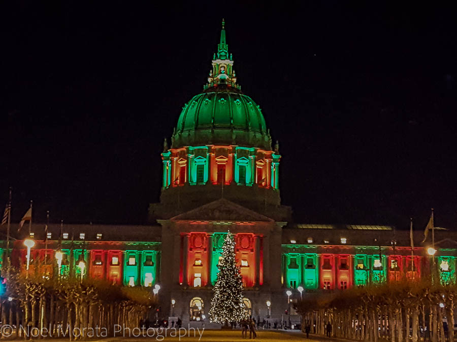San Francisco City Hall (big classical domed building) lit up in green and red against a black sky.