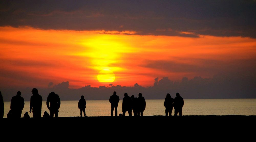 Sunset in Tuscany. In front, a row of people in sillouette. The sea beyond them with a spectacular orange and yellow sunset above the horizon. Photo courtesy of Sandy Swanton