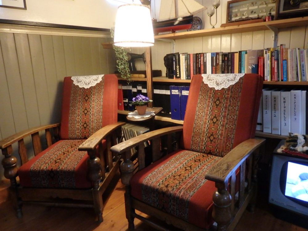 A comfortable corner of the living room in the Houseboat Museum: two armchairs in front of a bookshelf full of books.