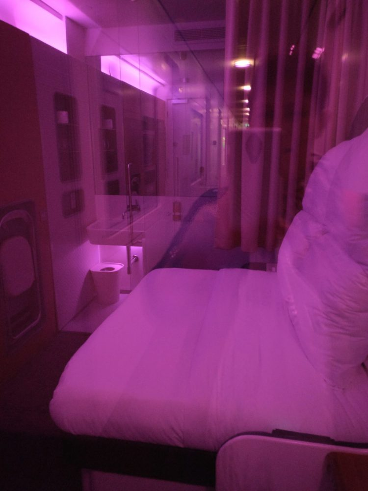A double room in the Yotel, as seen through the window from the hallway. The sex light is on.