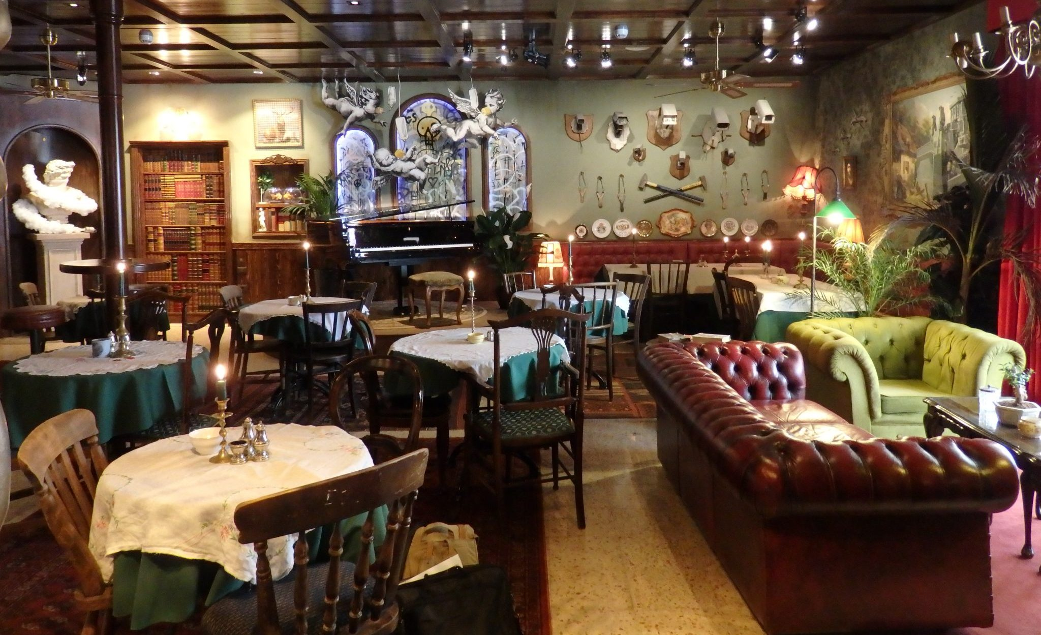 Visiting Bethlehem: The lobby and piano bar of the Walled Off Hotel. You can see the player piano on a raised platform in back, with cherubs in oxygen masks above it. Notice the mounted security cameras, and also the bookcase to the left, which is really a door.