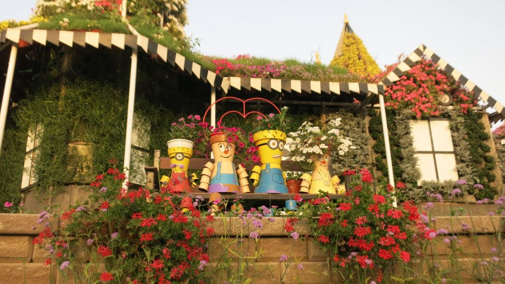"""Figures of people, made from flowerpots, sit on a bench in front of a flower-covered """"house"""" at Dubai Miracle Garden."""