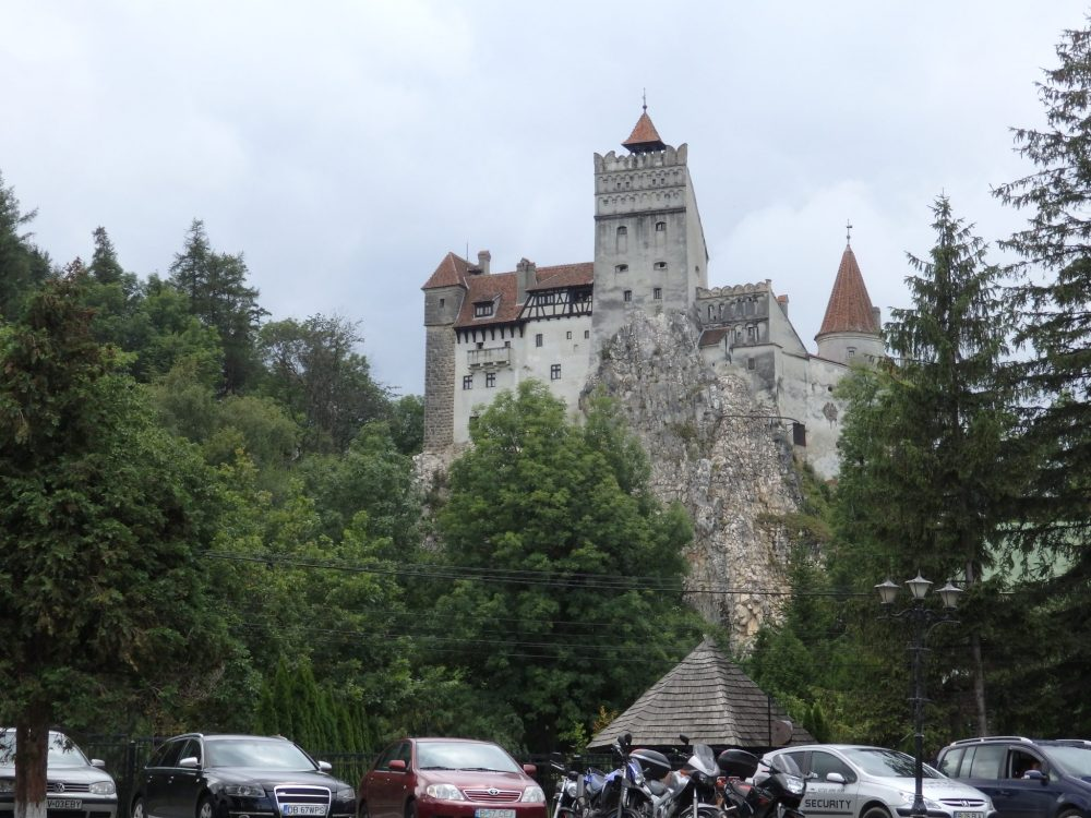A view upwards toward the castle. Cars parked at the bottom of the castle, a craggy rock and lots of trees behind them, and the grey castle with red roofs looms above.
