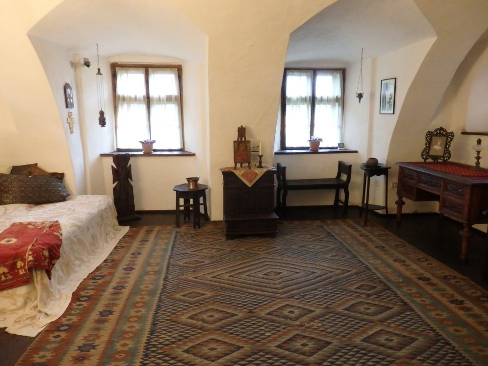 The floor is covered by a large dark carpet with geometric patterns on it. To the left is a bed with a cloth bedspread over it. Ahead are two windows with a small cupboard between them. A desk is to the right with a picture in a frame sitting on it.