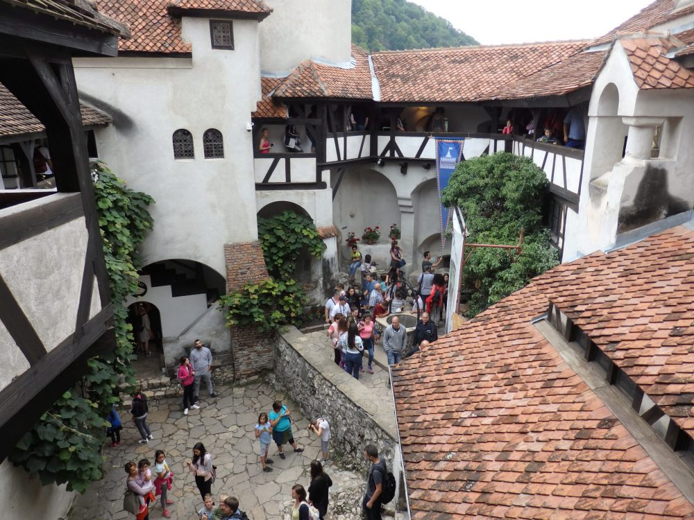 looking down into the courtyard of Bran Castle: stone floor below, white walls with half-timbered balconies sticking out, and red roofs. Lots of people are standing in the courtyard and the balconies opposite are also crowded with people.