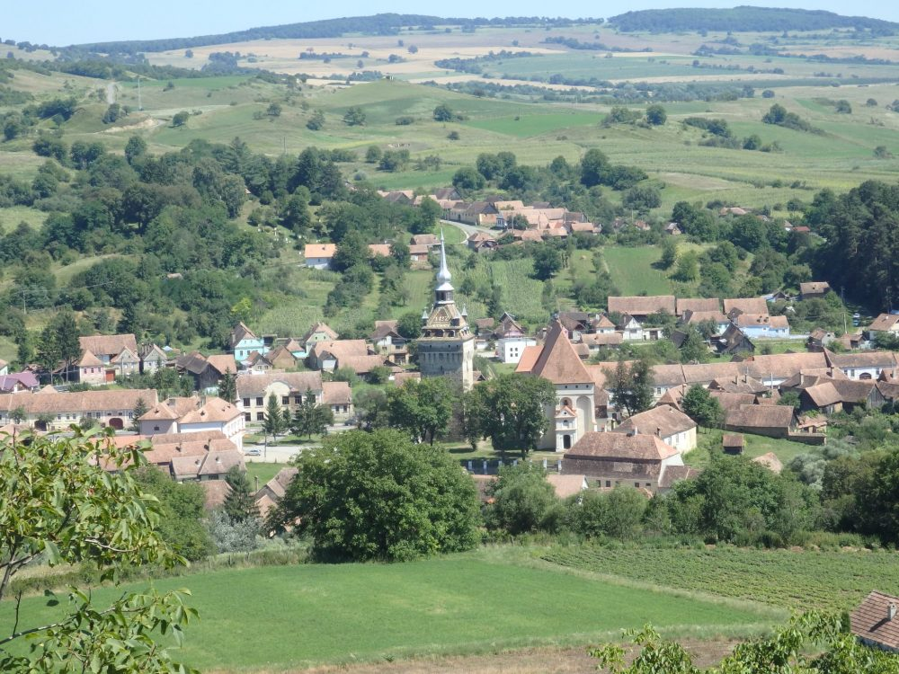Saschiz fortified church is in the center of this view, with the taller and fancier defensive tower and bell tower beside it.