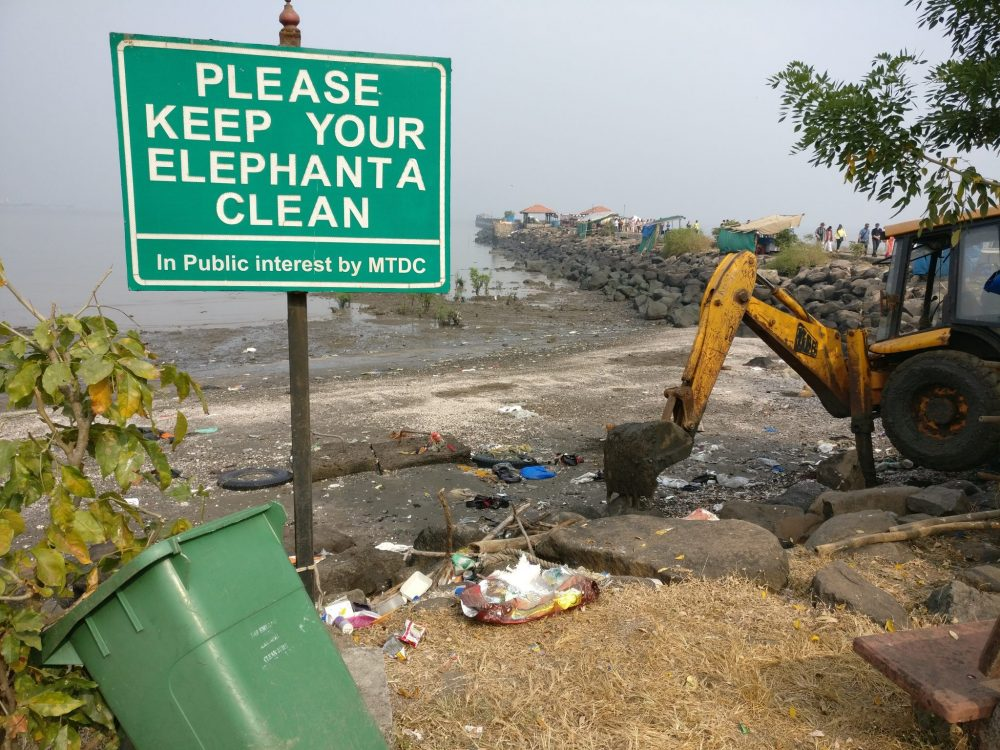 "A large sign on a pole reads ""Please keep your elephanta clean"" and, in smaller letters underneath ""In Public interest by MTDC"". Garbage is scattered on the ground under the sign. A green garbage bin is open and leaning against a shrub on the left. On the right is a small steamshovel. Behind this scene a beach is visible, edged by the long jetty. The beach is also strewn with trash."