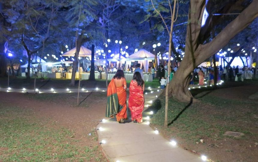 Women in colorful saris walk toward a wedding reception in the garden of our hotel.