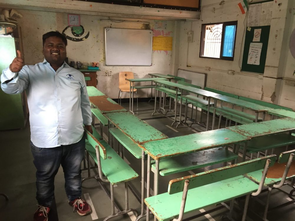 A classroom where Reality Gives conducts two sessions of school per day, with our guide, Jitu. We visited it on our Dharavi slum tour.