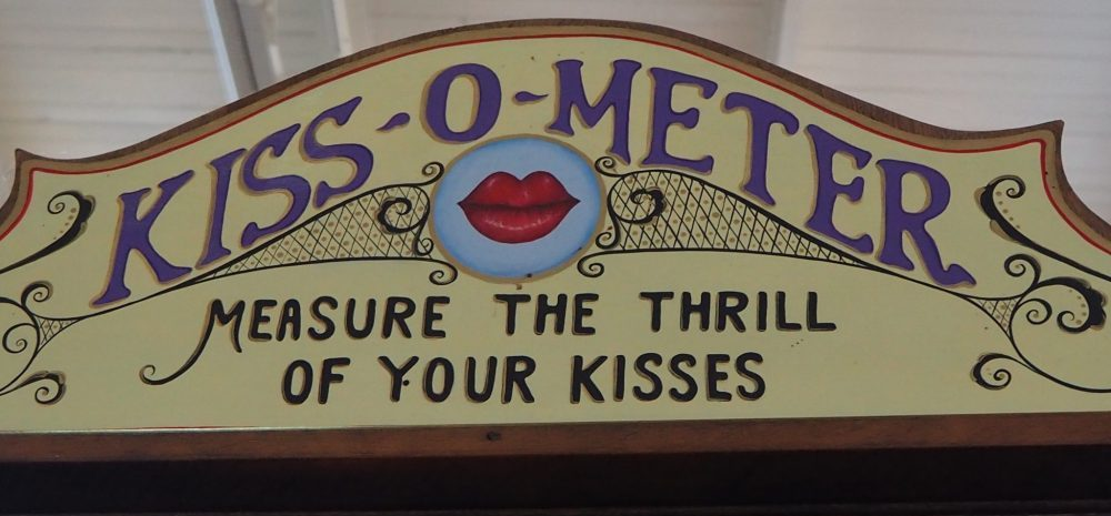 "The Kiss-o-meter instructions say ""Insert coin and kiss your mate."" A dial shows whether the kiss is passionate, exciting, sour, sweet, too hot lets go again, ice cold, sloppy keep trying, naughty, hot stuff, clammy, timid or amateurish."