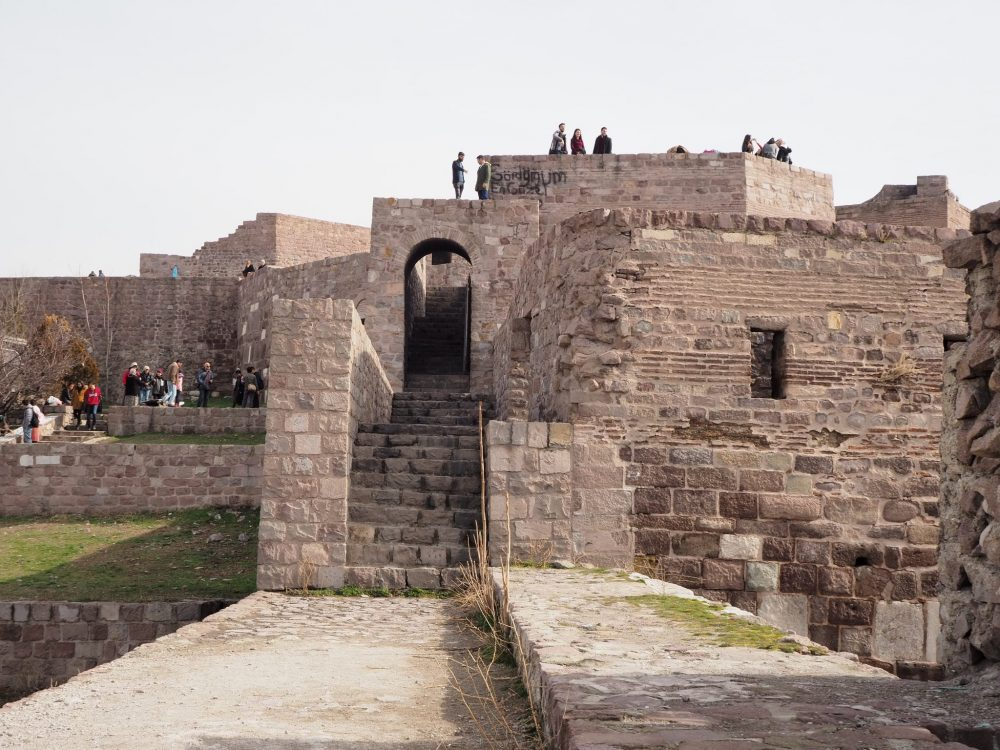 Straight ahead is a stone walkway and then a stairway, with stone walls on either side. The wall to the right of the stairway has alternating rows of stone blocks and much smaller red bricks. It has one small window in the middle of the wall. Other walls are visible in the background, and people stand on top of them.