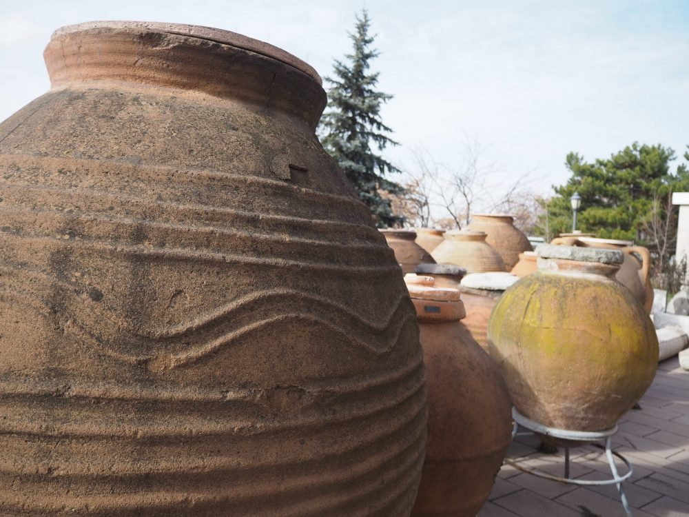 The pots are clay and quite large. The nearest one has simple lines in relief around the outside: some are wavy but most are straight horizontal lines. The pots behind are similar but many are not decorated at all. One in the photo has at least one handle on its side.