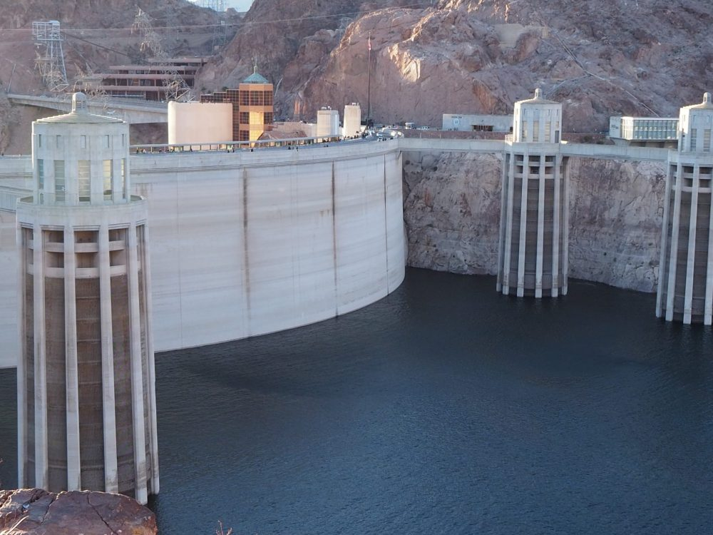 The curved dam on the left of the photo, dark blue water below. The intake towers are cylindrical. All of it is in whitish concrete, and the canyon walls behind it are a similar light rock color.