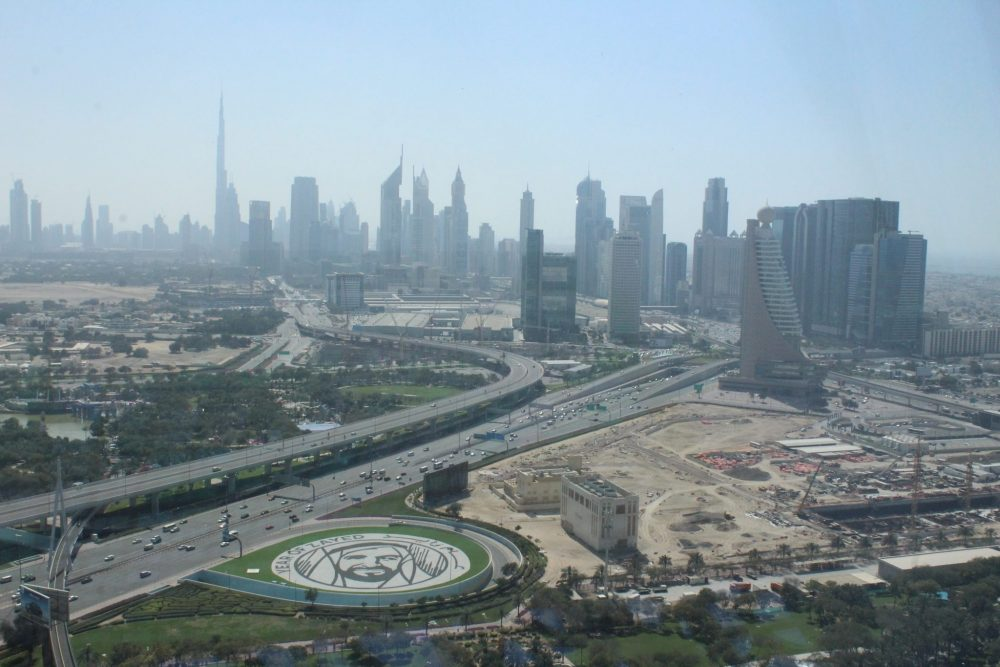 A highway extends from bottom left to middle right, with only a few low buildings and building sites in the foreground, along with a very neat circle within a highway exit, planted with something in the shape of a man's head, presumably a sheik. In the background are a range of tall buildings, skyscrapers, a bit fuzzy because of the smog/dust. The sky beyond them is a pale blue.