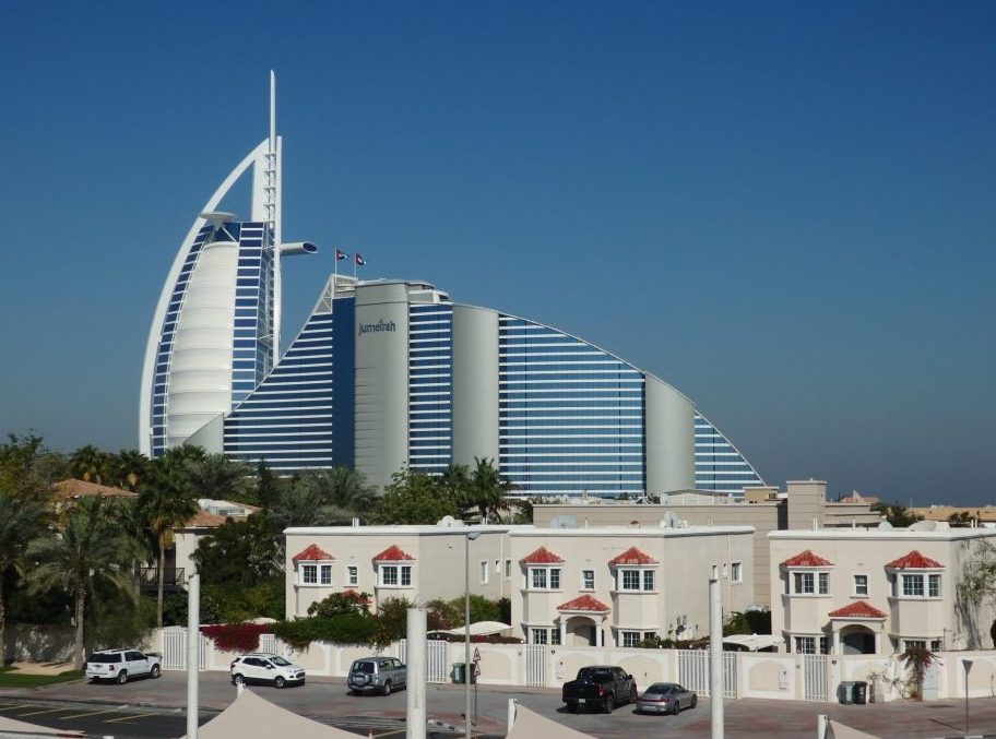 The Burj Al Arab behind the equally upscale Jumeirah Beach Hotel in Dubai.