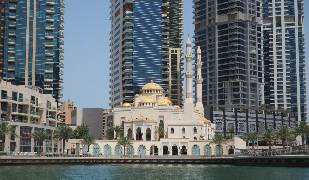 A mosque in the Dubai Marina, surrounded by tall buildings, some finished and some unfinished.