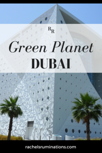 Pinnable image Text: Green Planet Dubai Image: the building: white with round holes, with the corner in the center of the picture. Two palm trees at the bottom of the picture in front of the building.