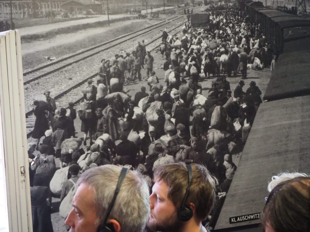 Visitors shuffle past a large photo of prisoners being off-loaded from the trains at Auschwitz.