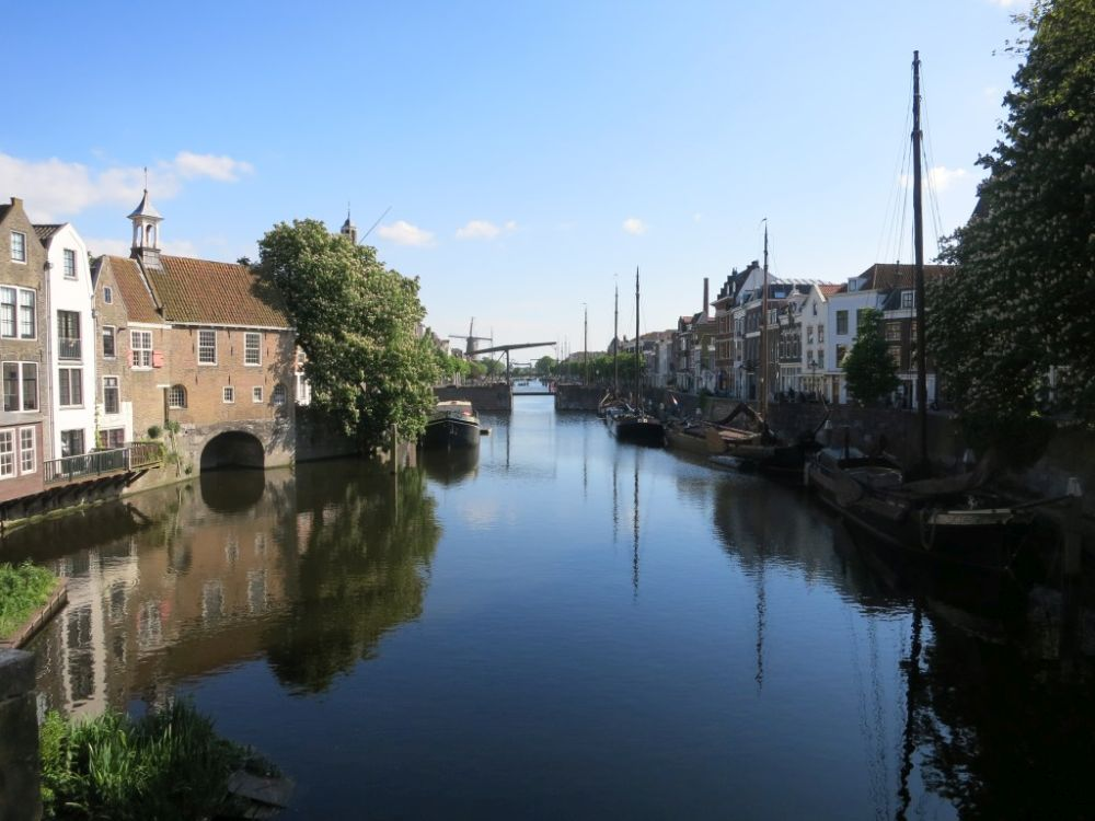 Looking down a canal, the water is still and reflects the buildings on either side. The buildings that are visible are typical narrow brick warehouse buildings.