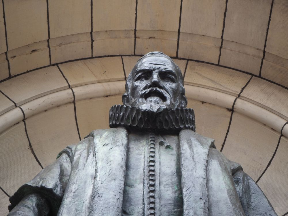 Looking up at the metal statue, only the chest and head are visible. The man is bearded and looks severe. He has a ruffly collar around his neck and wears robes.