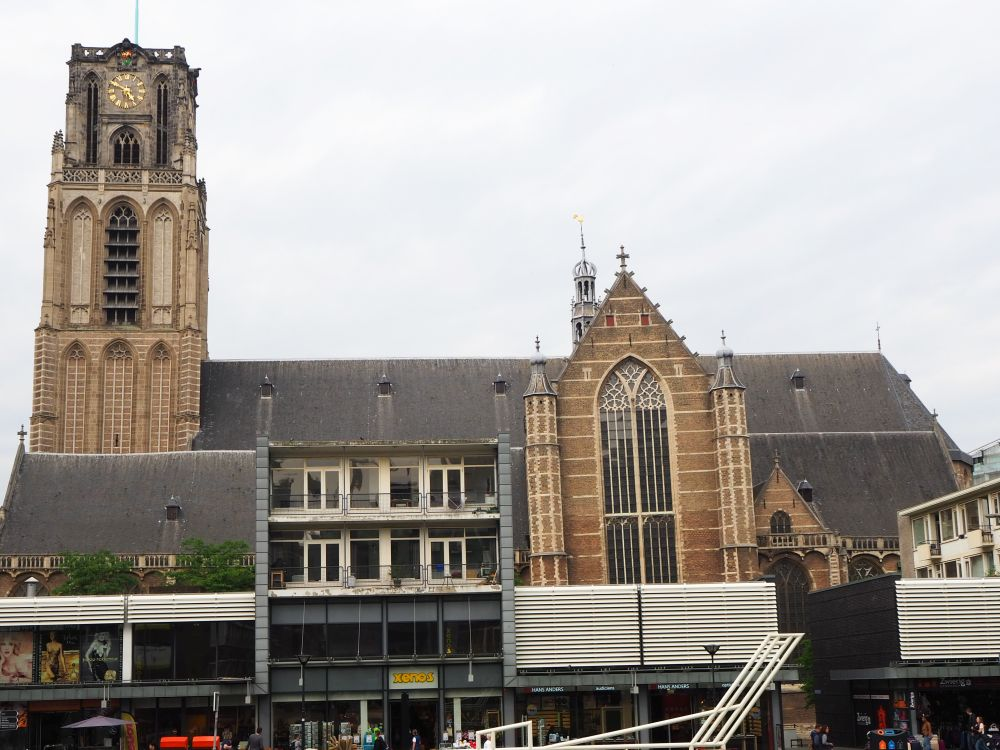 The church is seen from the side, with the church tower on the left. About halfway down the side, a large gothic window is visible. The rest of the building is hidden behind some modern buildings in front: shops with apartments above them, about 3-4 stories tall.