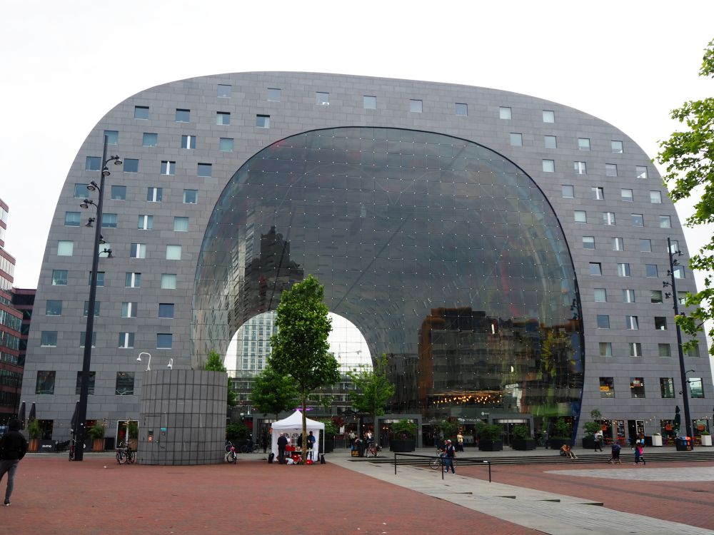 The Markthal is in the form of a large half-tube or U, so that the market itself is sheltered underneath. It is grey and dotted with windows. The open part underneath is fronted with a huge glass wall.